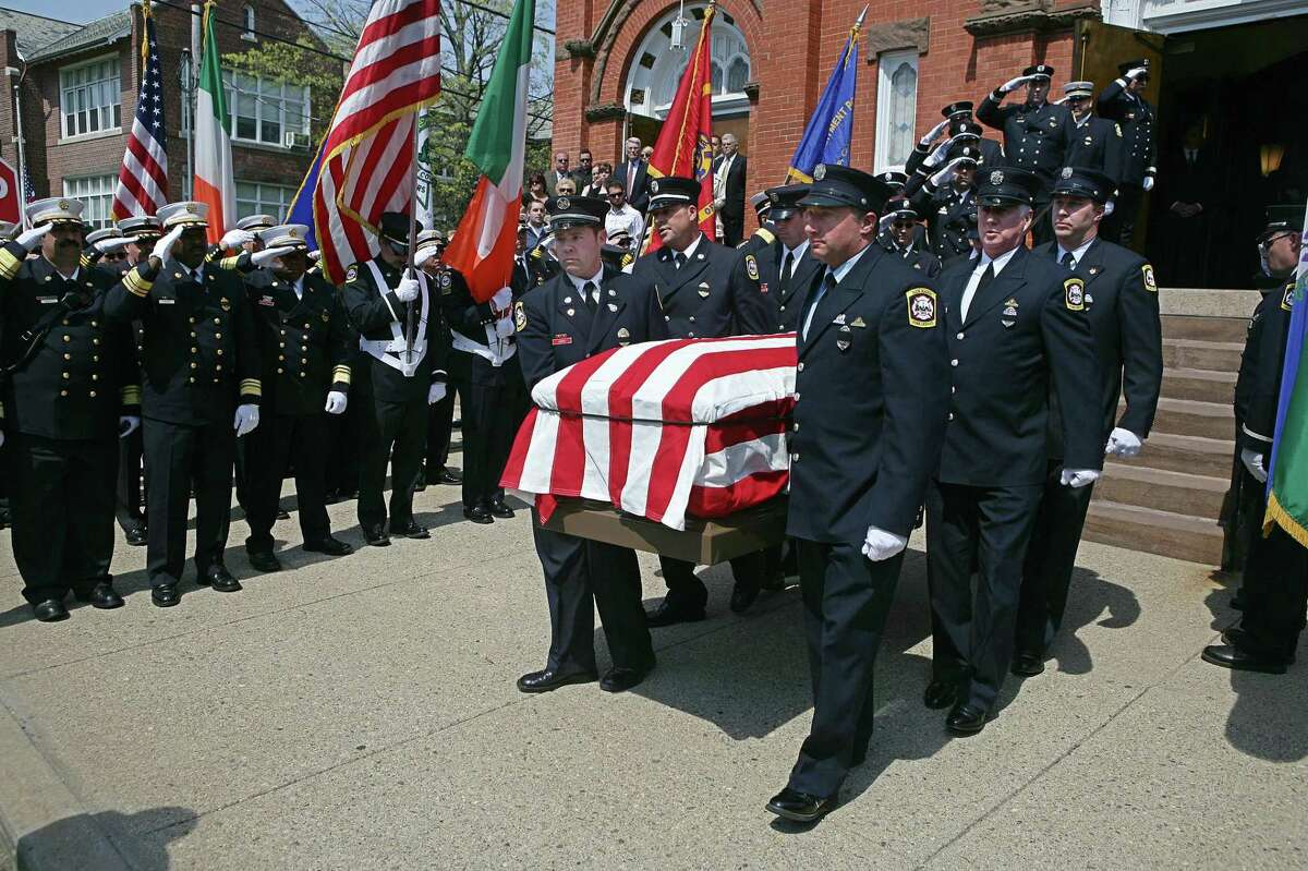 Firefighters carry the casket of New Haven Firefighter Patrick Reardon out of St. Lawrence Church in West Haven in April 2009.