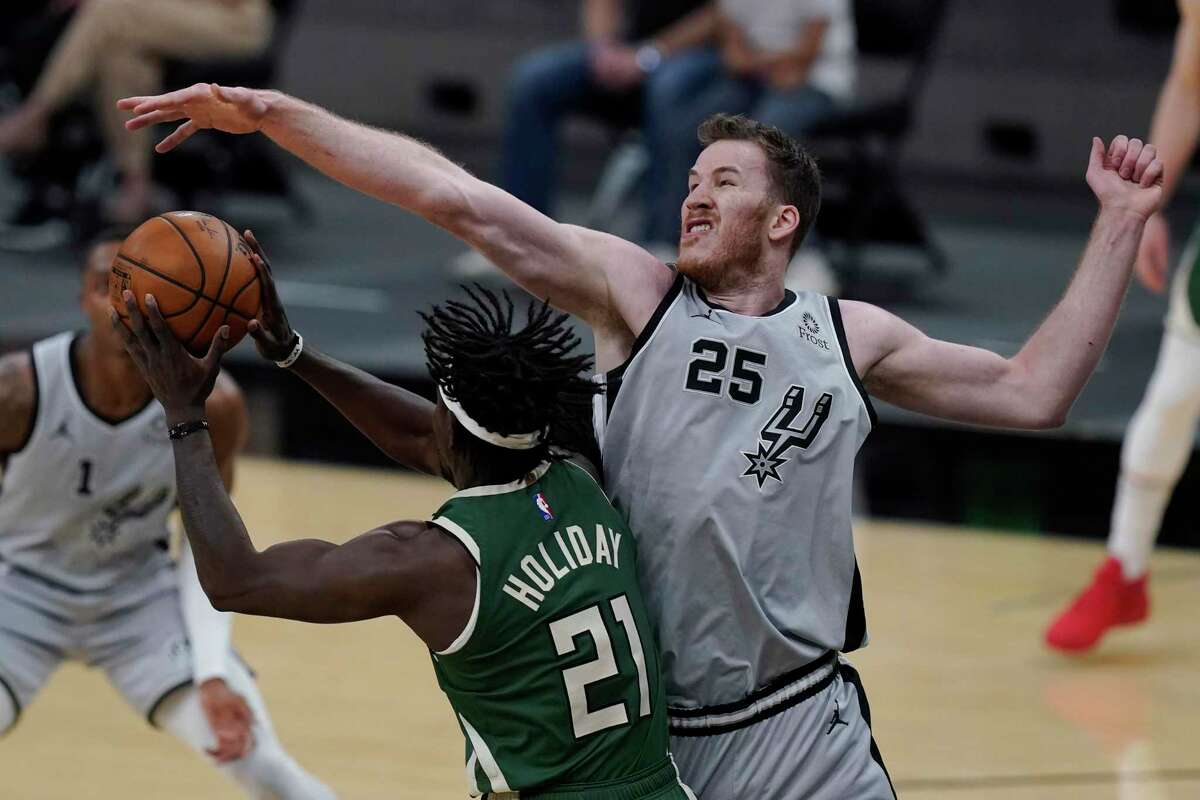Milwaukee Bucks guard Jrue Holiday (21) is defended by Spurs center Jakob Poeltl (25) during the first half of an NBA basketball game in San Antonio, Monday, May 10, 2021.