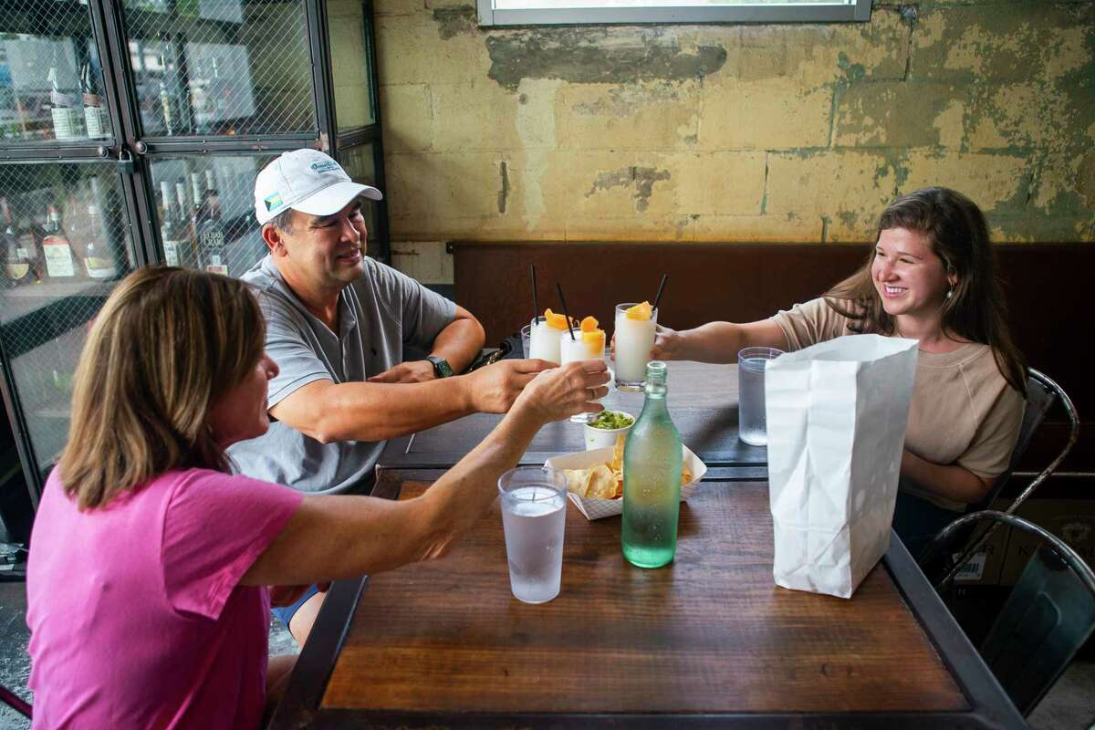 Barb and John Barajas toast with their daughter Kelsey, Friday, May 22, 2020, at Eight Row Flint in Houston on the first day that bars were allowed to reopen in Texas.