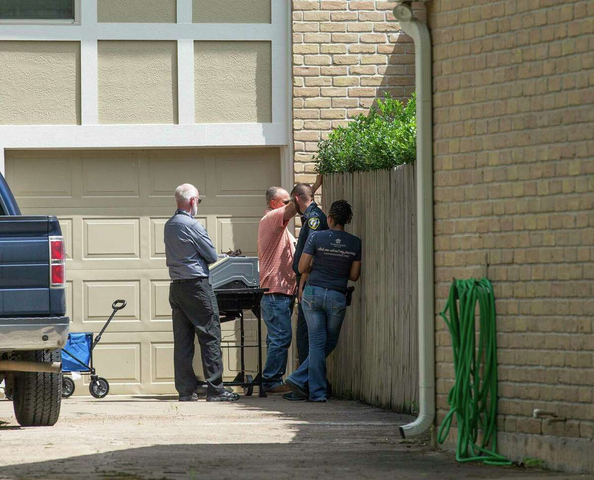 Law enforcement officials investigate, Monday, May 10, 2021, in Houston, the house where a tiger, which was loose the night before on the 1100 block of Ivy Wall Drive, was being kept. (Godofredo A. Vásquez/Houston Chronicle via AP)