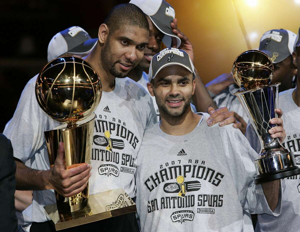 Cleveland, UNITED STATES: Frenchman Tony Parker (R) of the San Antonio Spurs holds the MVP trophy with teammate Tim Duncan (L) holding the NBA Championship Larry O'Brien trophy after leading the San Antonio Spurs to their fourth NBA title beating the Cleveland Cavaliers 14 June 2007 after Game Four of the NBA Finals at Quicken Loan Arena in Cleveland, Ohio. The Spurs won the game 83-82 to win the best-of-seven game series 4-0. AFP PHOTO/JEFF HAYNES (Photo credit should read JEFF HAYNES/AFP via Getty Images)