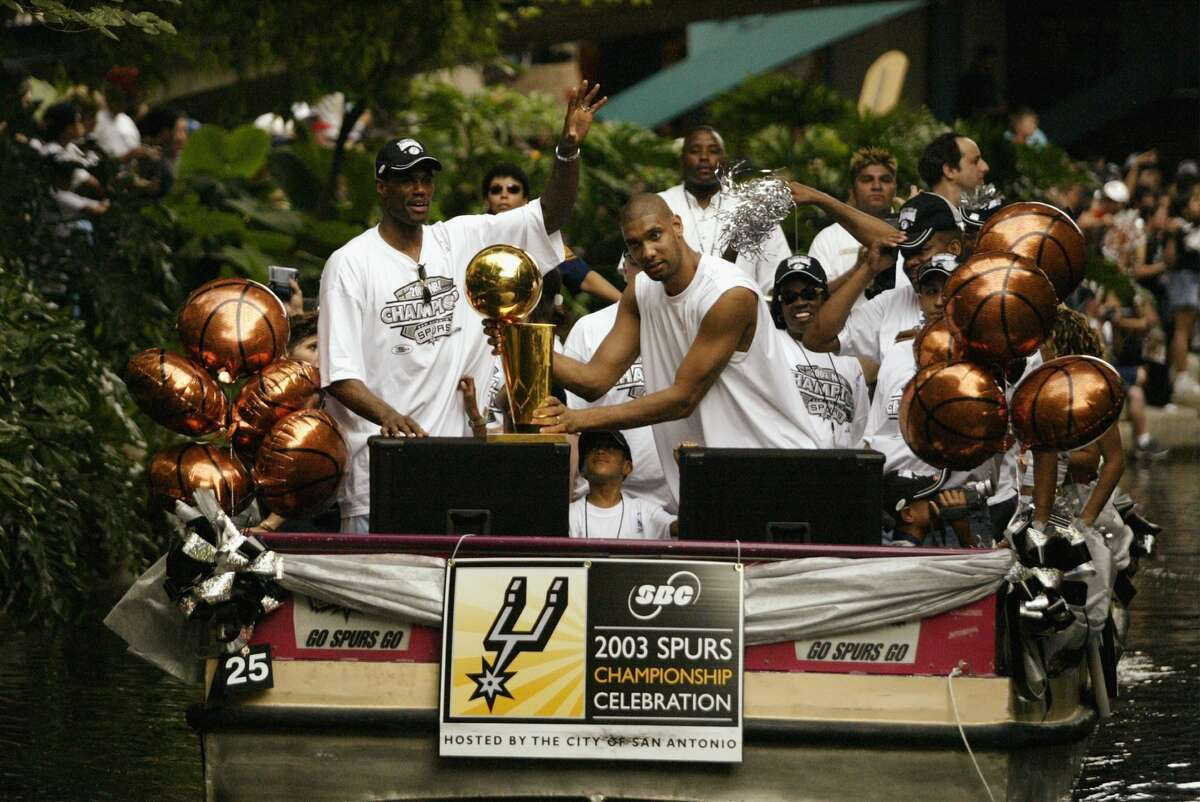 SAN ANTONIO - JUNE 18: (L-R) David Robinson #50 and Tim Duncan #21 of the San Antonio Spurs celebrate with the 2003 NBA Championship trophy during the SBC 2003 Spurs Championship Celebration on June 18, 2003 at the Riverwalk in San Antonio, Texas. NOTE TO USER: User expressly acknowledges and agrees that, by downloading and/or using this Photograph, User is consenting to the terms and conditions of the Getty Images License Agreement. (Photo by Ronald Martinez/Getty Images)