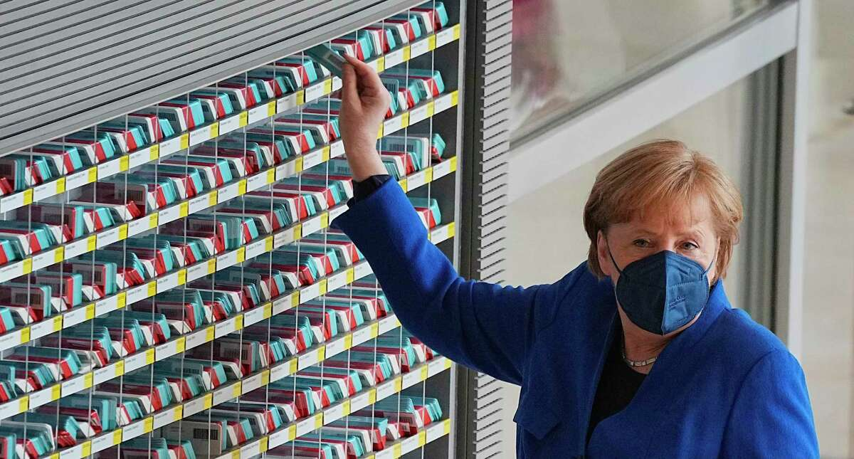 German Chancellor Angela Merkel takes her voting card in the Bundestag in Berlin, Germany, Thursday, May 6, 2021. The Bundestag voted on the Infection Protection Act, which provides for relief and exemptions from protective measures to prevent the spread of Covid-19. (Michael Kappeler/dpa via AP)