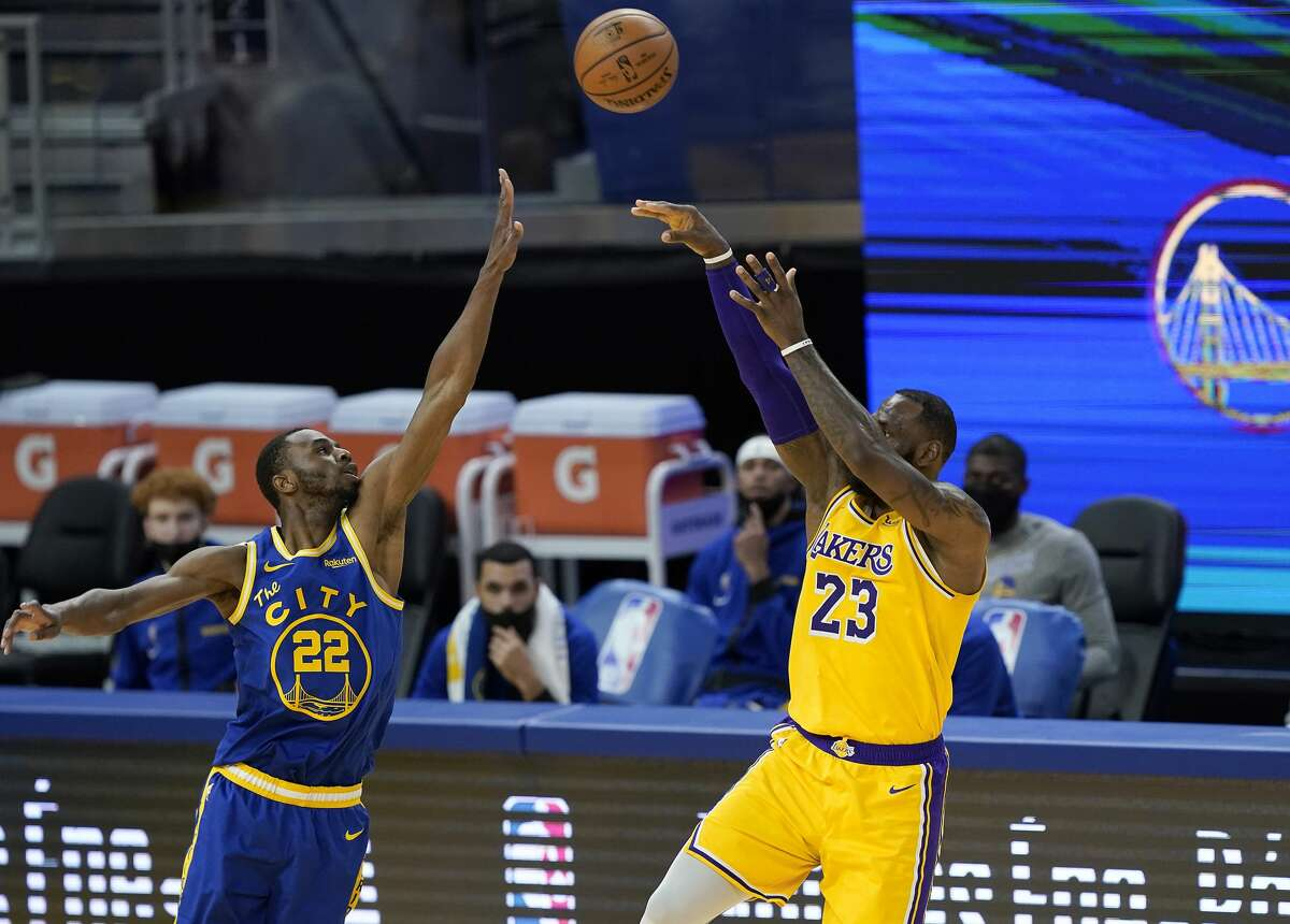 LeBron James of the Los Angeles Lakers shoots over Andrew Wiggins of the Golden State Warriors during the second half of an NBA basketball game at Chase Center on March 15, 2021.