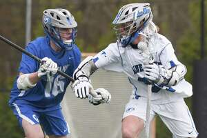 Darien's Brady Pokorny (99) battles Glastonbury's Ryder Harmon (16) during a game in April.