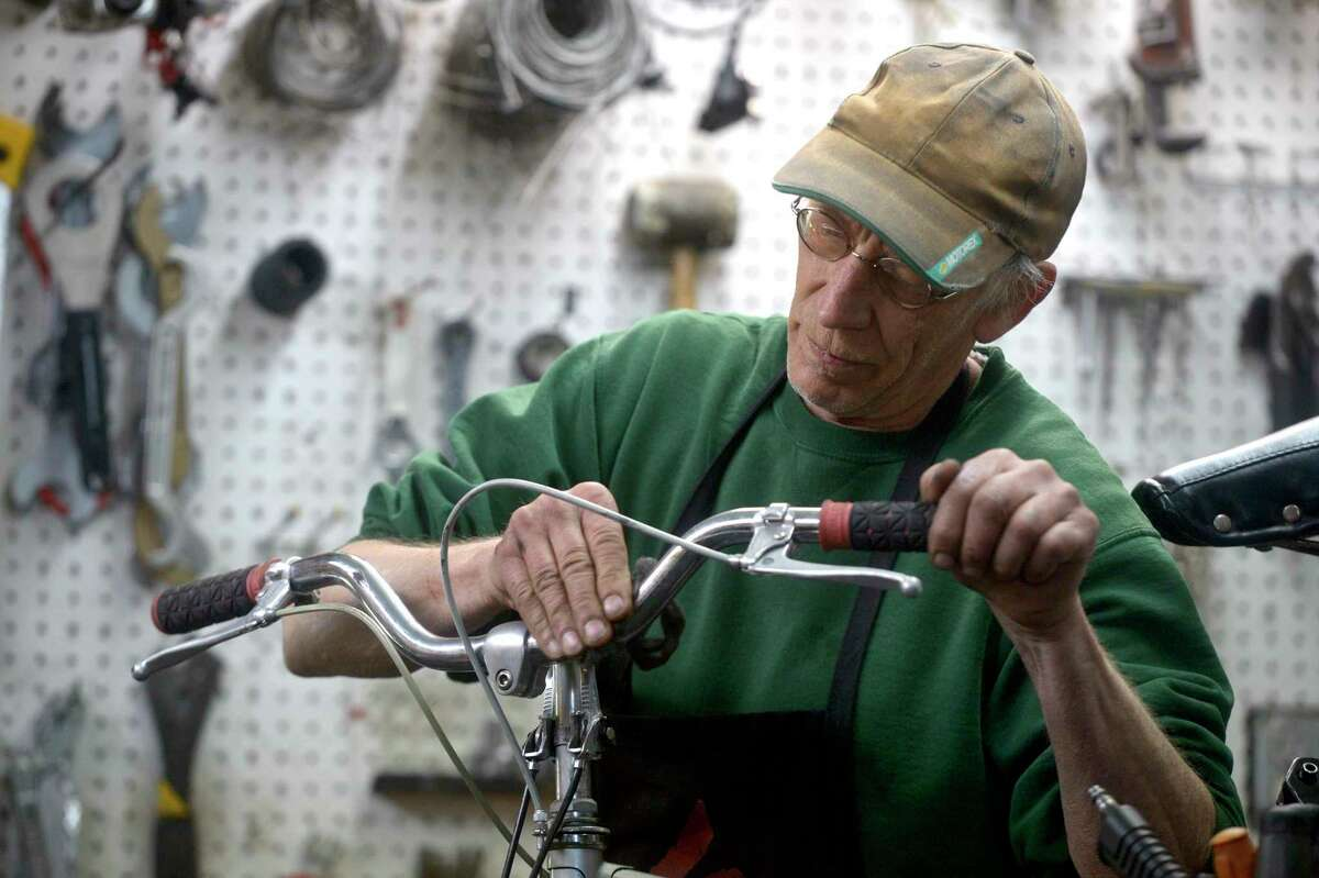 John Gallagher, owner of The Bike Express of New Milford, works on a bike in his workshop. Gallagher who has owned the shop since 1985, when he bought the shop, has put it up for sale. Wednesday, May 12, 2021, in New Milford, Conn.