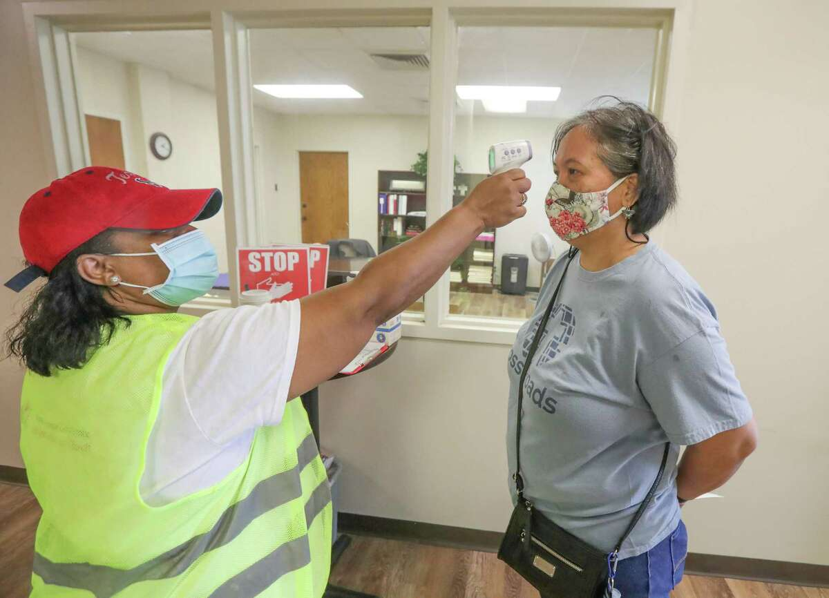 Valencia Wiltz takes volunteer Lora Cook's temperature before a COVID-19 vaccine clinic for the community at CrossRoads United Methodist Church Friday, April 30, 2021, in Houston.
