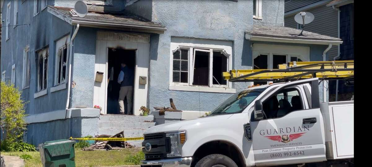 An investigator enters a home on Rosemary Street in New London after an arson fire on Tuesday morning.