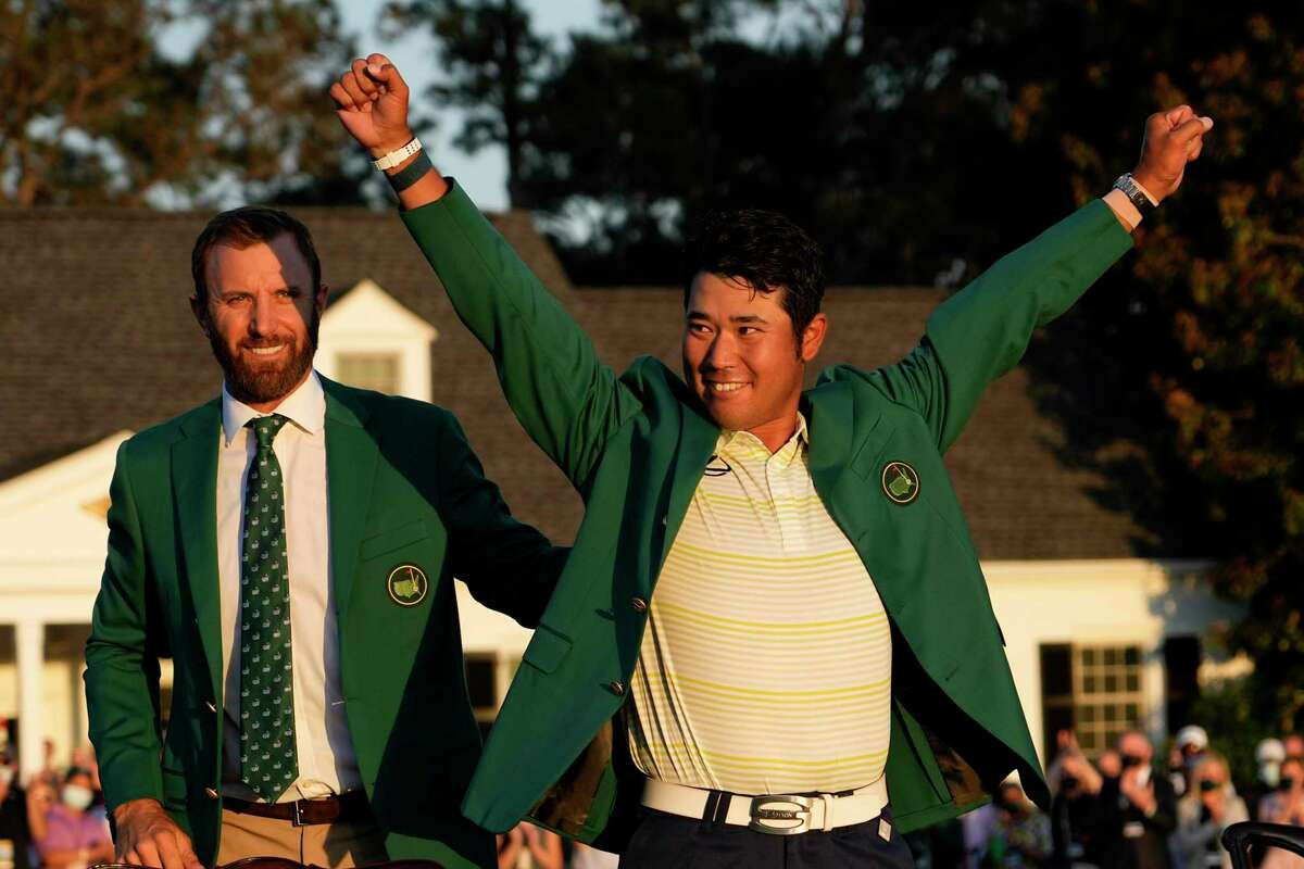 Hideki Matsuyama of Japan puts on the champion's green jacket after winning the Masters in Augusta, Ga., in April. Last year's winner, Dustin Johnson, is at left.