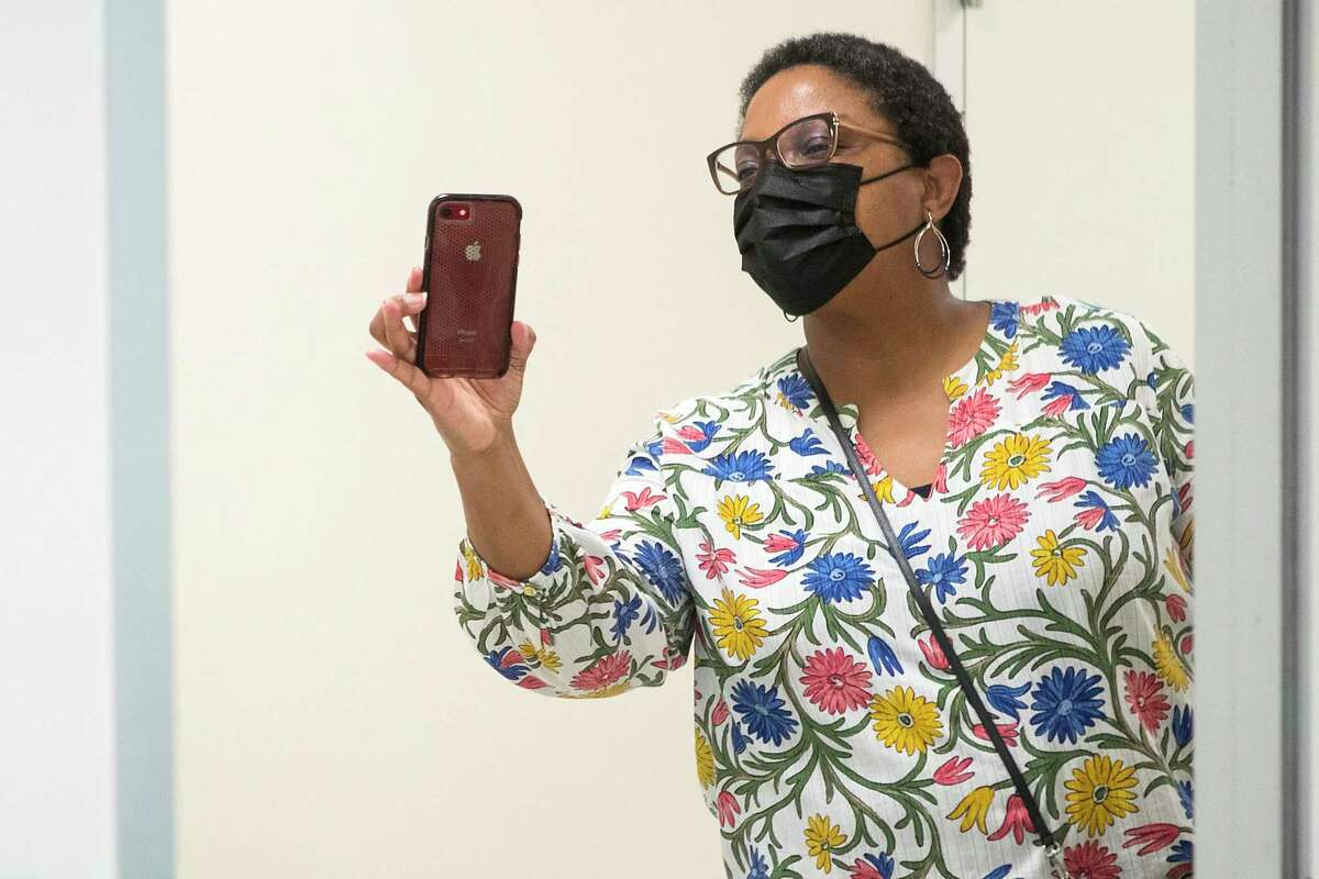 Angela Gant leans in to capture a video of her daughter Kennedy's first dose of the Pfizer vaccine.