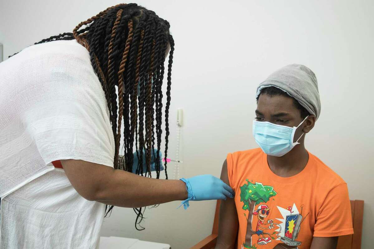 Registered nurse Ellena Steward-Scott administers a dose of the Pfizer BioNTech COVID-19 vaccine to her son, Collin Scott, 13, at Baylor College of Medicine Wednesday, May 12, 2021 in Houston. Scott was in the group of first teenagers to receive the COVID-19 vaccine in the Houston area, less than two hours after federal health officials officially recommended the distribution of the vaccine to 12- to 15-year-olds nationwide.