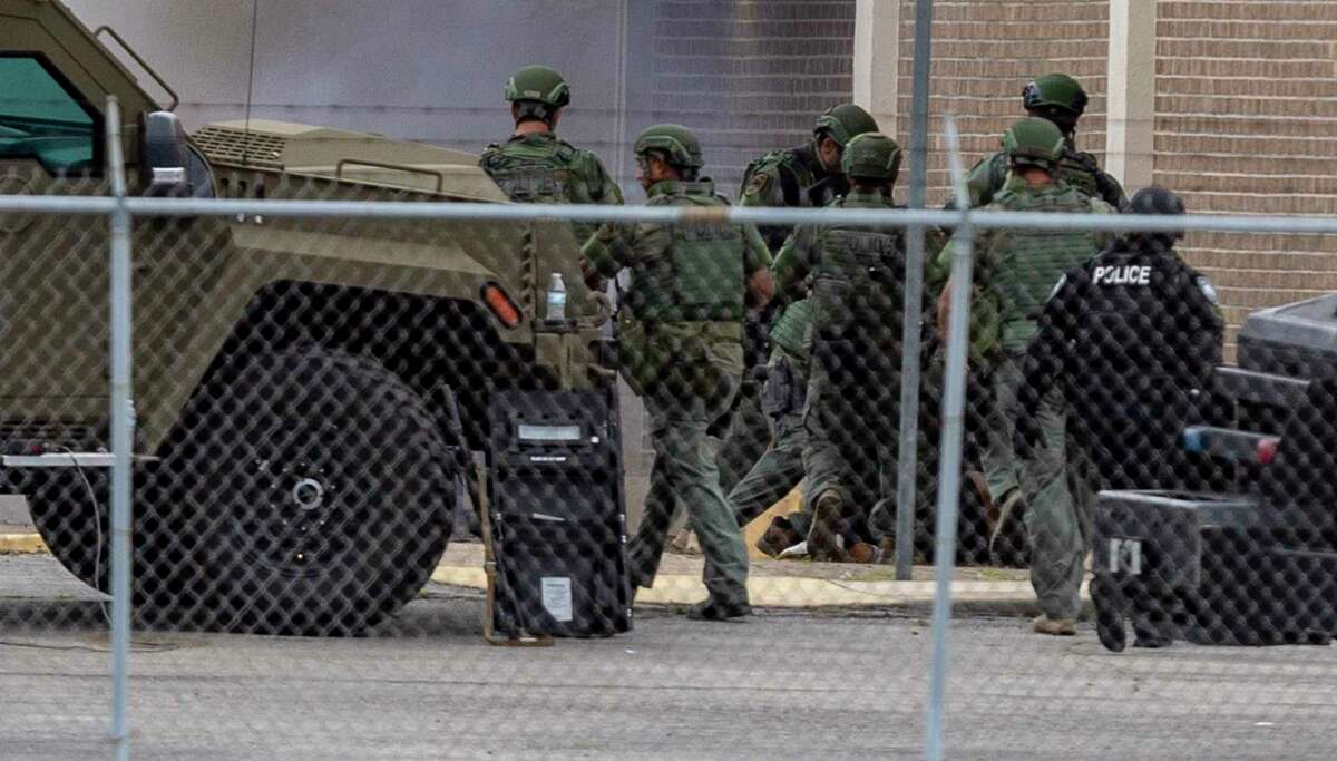 """San Antonio police department SWAT team members swarm over a man Wednesday, May 12, 2021 near South New Braunfels and Ada Lane after what appeared to be a """"flash-bang"""" grenade thrown by the team detonated next to him. Police had been in a stand-off with the man since Tuesday night. The man had said he was suicidal, according to police."""