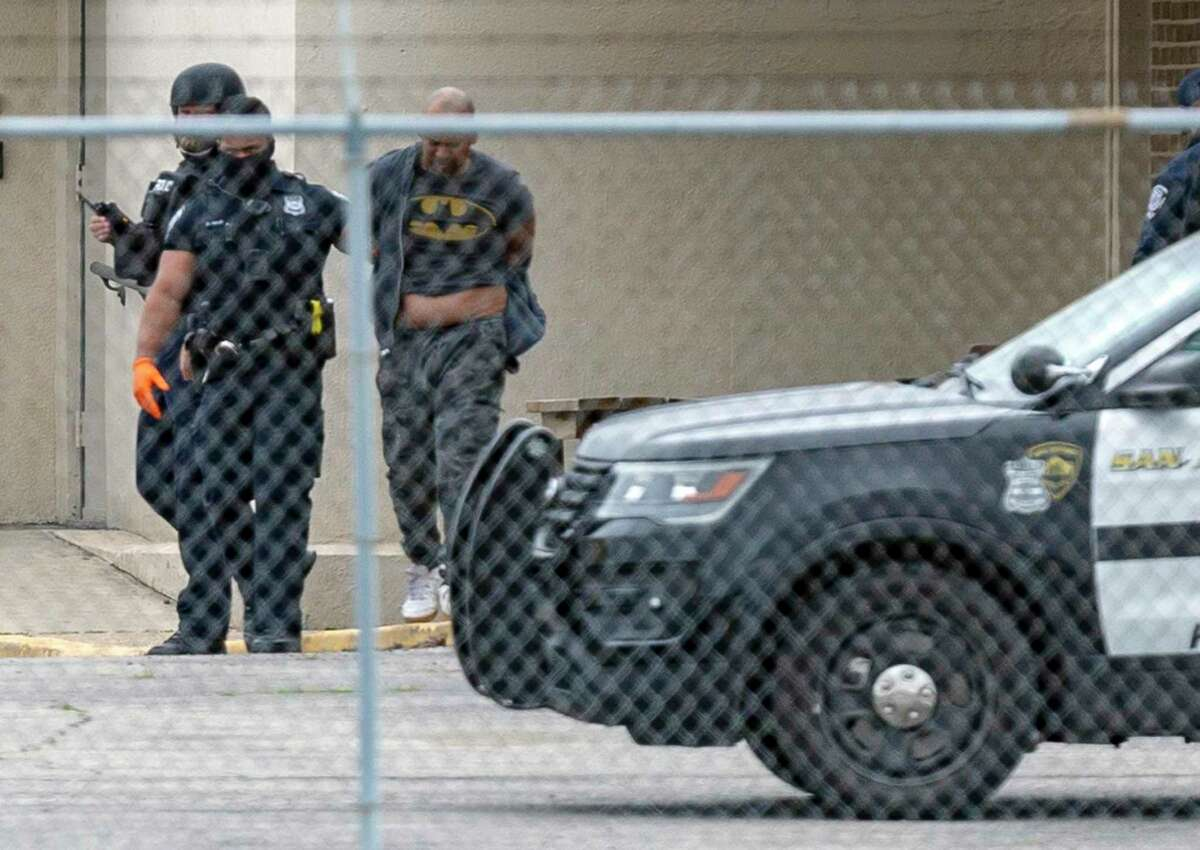 San Antonio officers escort the suspect to a police car about 10 a.m. Wednesday. Police said the man had said he was suicidal.