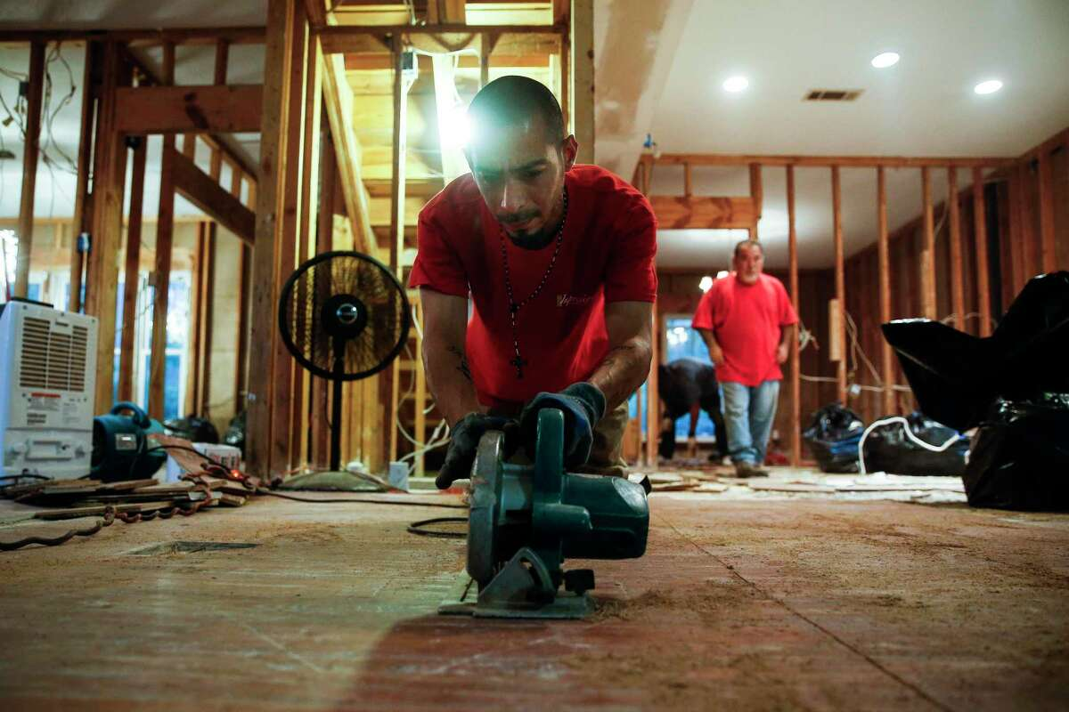 Hurricane Harvey devastated Houston and the Kingwood area, which did make changes to help prevent flooding again in the future, but now as individuals and businesses aim to rent or buy property, flooding is considered less important now than factoring in a pandemic. Pictured: Contractor Rick Cervantes, with Alfred C. Schuley Hardwood Floors, cuts up the floors at Carolanne Norris' home that flooded during Hurricane Harvey Tuesday, Oct. 3, 2017 in Kingwood. Norris believes that the release from the Lake Conroe dam is responsible for flooding her home. ( Michael Ciaglo / Houston Chronicle)
