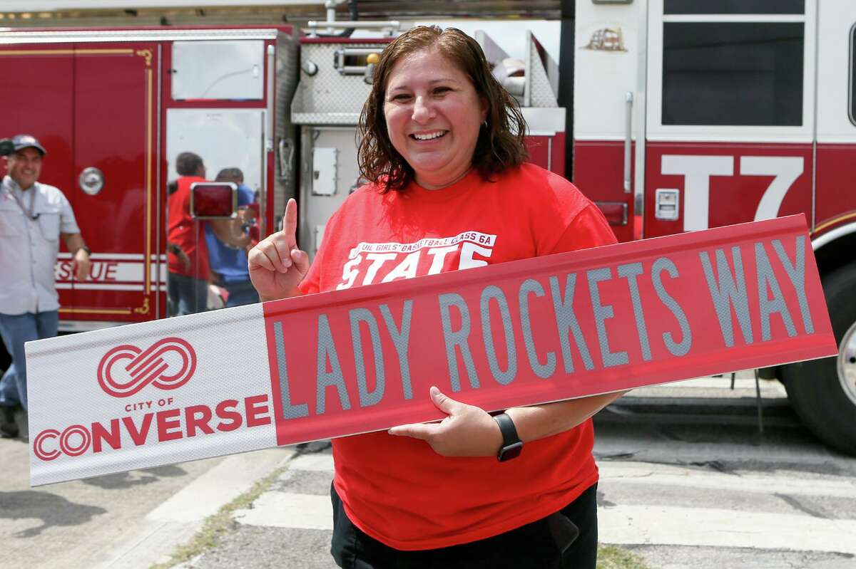 """Judson girls basketball coach Triva Corrales holds a replica """"Lady Rockets Way"""" street sign during a ceremony changing the name of part of Lower Seguin Road by the city of Converse on Friday, May 17, 2019. The city of Converse renamed the street in honor of their class 6A girls state basketball championship this past season."""