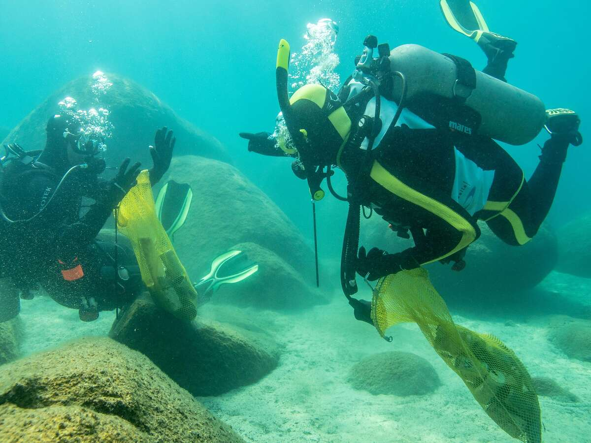 Divers pick trash out of the rocks in Lake Tahoe.