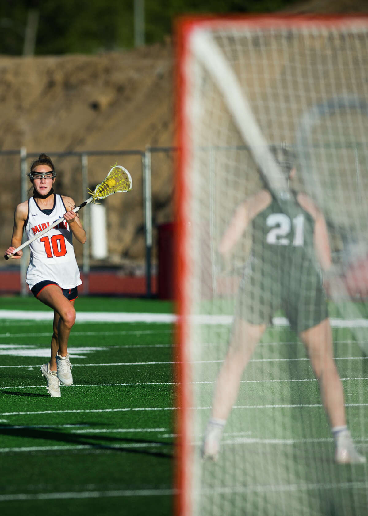 Midland's Emma Murphy moves the ball down the field during a game against Lake Orion Wednesday, May 12, 2021 at Midland Community Stadium. (Katy Kildee/kkildee@mdn.net)