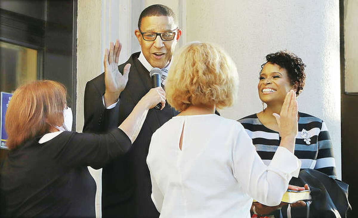 David Goins is sworn in as mayor of the city of Alton by outgoing Alton City Clerk Mary Boulds, center, with his wife, Sheila Goins, right, at his side Wednesday evening on the steps of Alton City Hall. A crowd of about 400 people gathered to watch the ceremony.