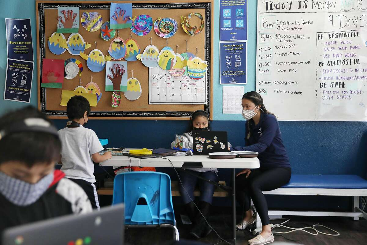 Desiree Almeida (right), health and fitness coordinator, works with Giselle, 9, at the elementary school learning hub, part of the Tenderloin Clubhouse campus.
