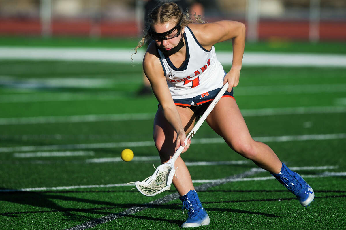 Midland's Delaney Abbott scoops up the ball during a game against Lake Orion Wednesday, May 12, 2021 at Midland Community Stadium. (Katy Kildee/kkildee@mdn.net)