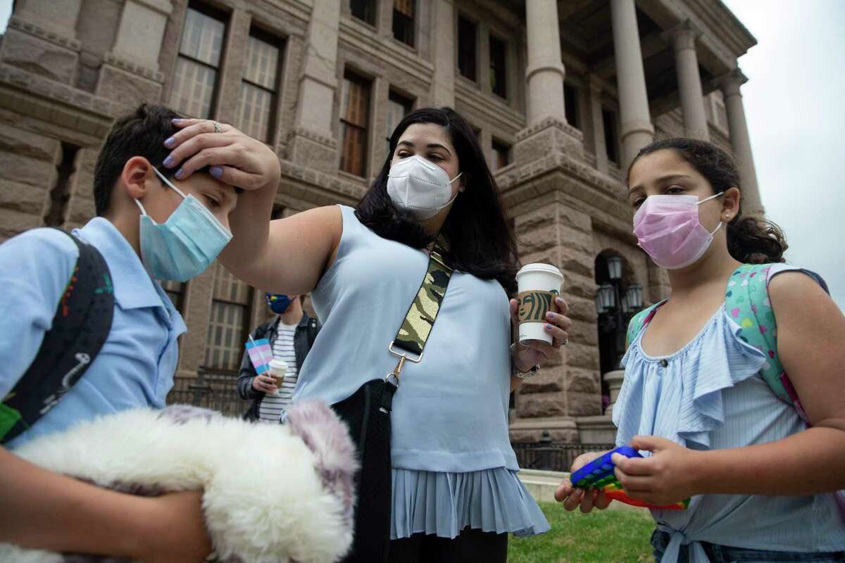 Max Stanton offers his pop fidget toy to his transgender sister, Maya Stanton, both 10, to allay her stress on Saturday, May 8, 2021, in Austin. The Stanton family went to the Texas Capitol along with a group of transgender families to speak out against bills in the legislature that will affect their lives.