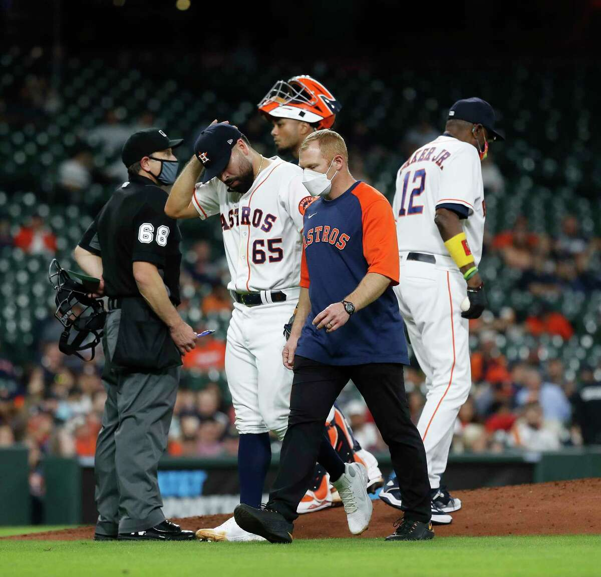 Astros starting pitcher Jose Urquidy departs the mound with athletic trainer Lee Meyer during the fourth inning Wednesday night at Minute Maid Park.
