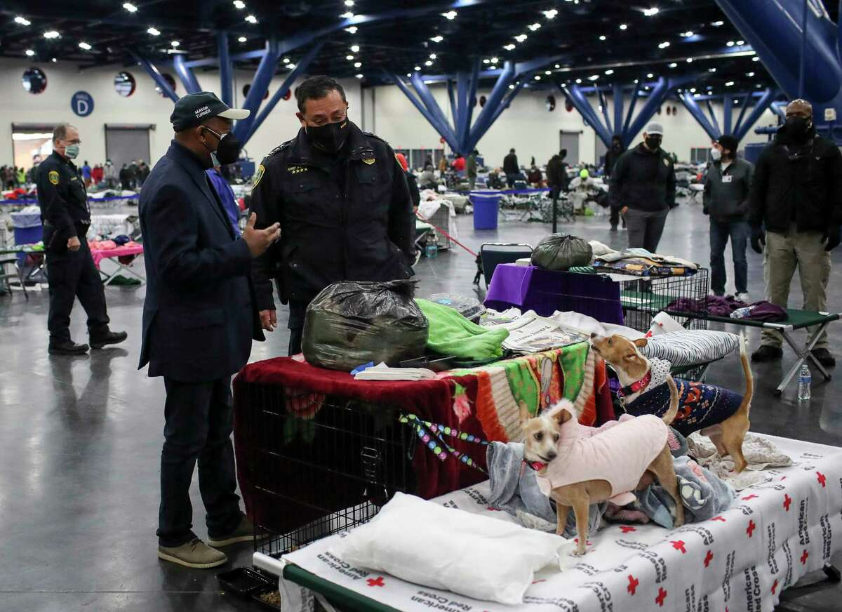 Houston Mayor Sylvester Turner, left, and Houston Police Chief Art Acevedo are greeted by two barking dogs as they tour a city warming shelter Wednesday, Feb. 17, 2021, at the George R. Brown Convention Center in Houston.