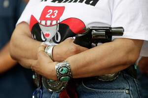 Dr. Alma Arredondo-Lynch holds a pistol as gun rights advocates gather outside the Texas Capitol where Texas Gov. Greg Abbott held a round table discussion, Thursday, Aug. 22, 2019, in Austin, Texas. Abbott is meeting in Austin with officials from Google, Twitter and Facebook as well as officials from the FBI and state lawmakers to discuss ways of combatting extremism in light of the recent mass shooting in El Paso that reportedly targeted Mexicans. (AP Photo/Eric Gay)