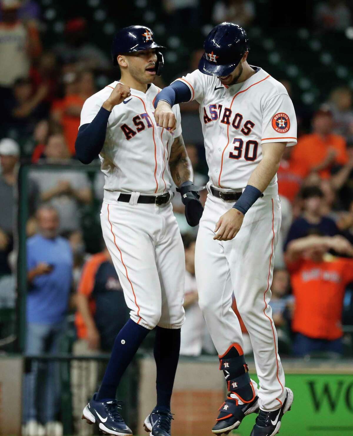 Houston Astros right fielder Kyle Tucker (30) celebrates his home run off of Los Angeles Angels starting pitcher Andrew Heaney with Carlos Correa during the sixth inning of an MLB baseball game at Minute Maid Park, Wednesday, May 12, 2021, in Houston.