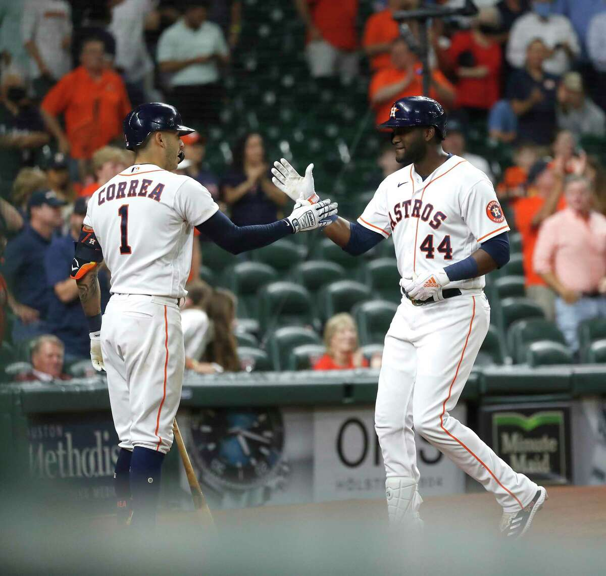 Astros designated hitter Yordan Alvarez (44) celebrates with Carlos Correa after hitting a home run off during the eighth inning Wednesday at Minute Maid Park.
