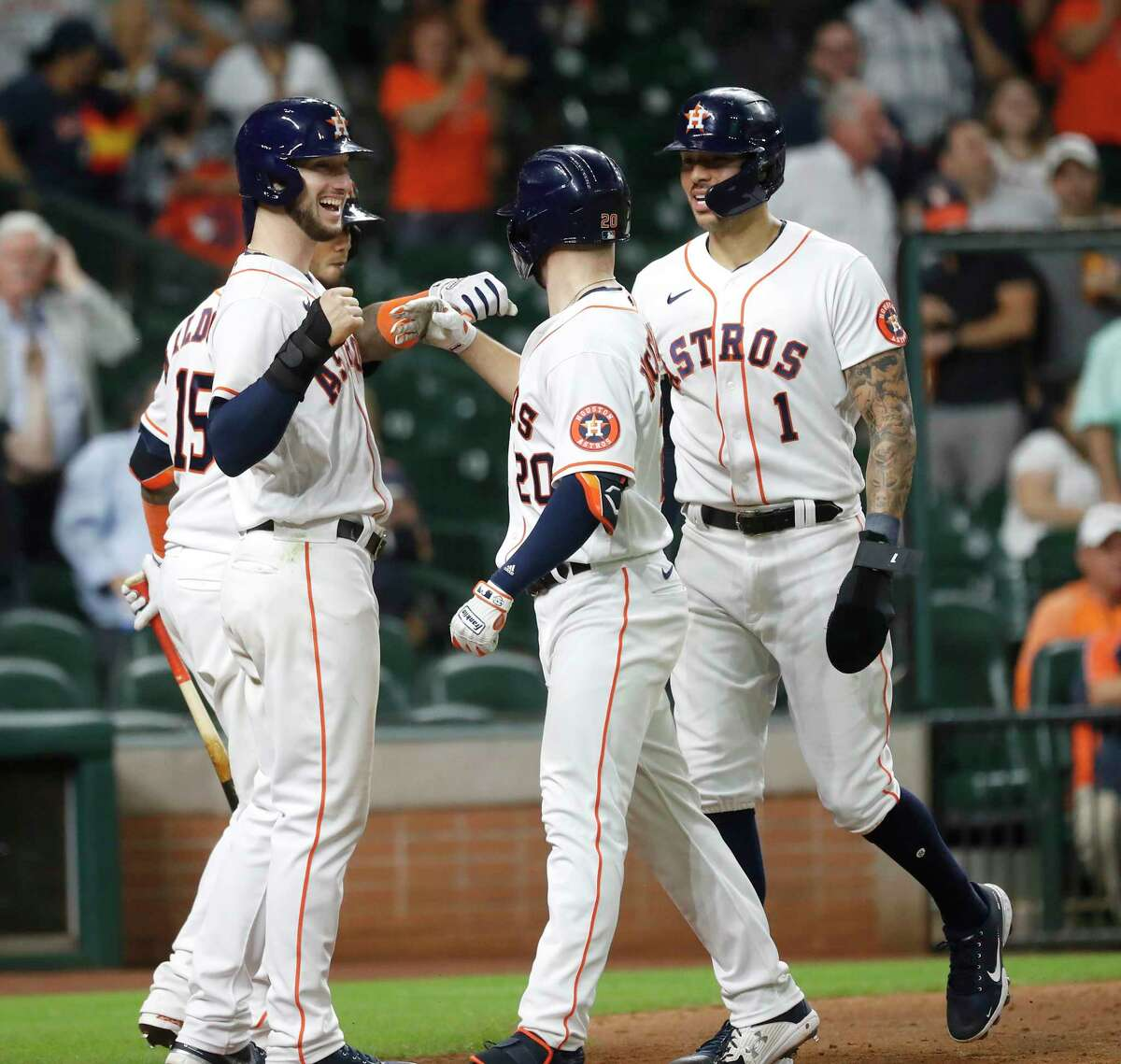 Houston Astros Chas McCormick (20) celebrates with Carlos Correa and Kyle Tucker after hitting a three-run home run off of Los Angeles Angels pitcher Patrick Sandoval during the eighth inning of an MLB baseball game at Minute Maid Park, Wednesday, May 12, 2021, in Houston.