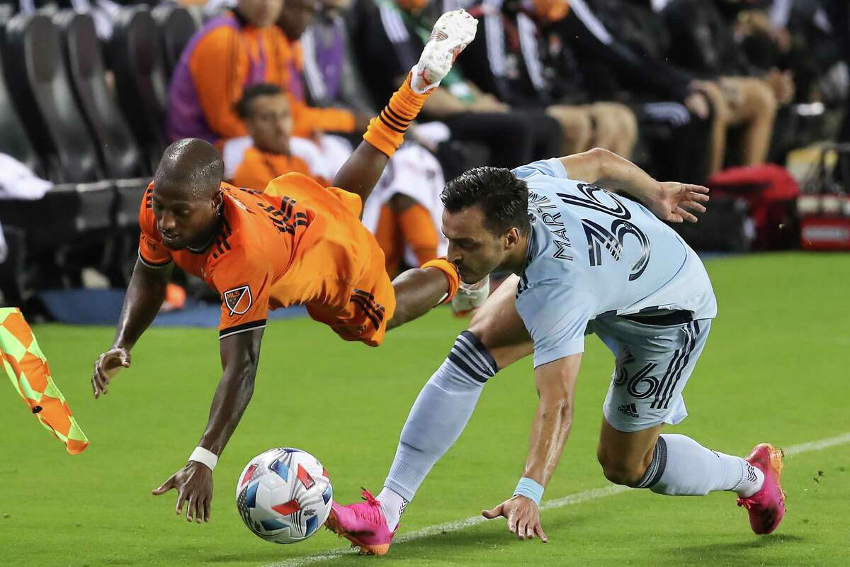 Houston Dynamo midfielder Fafa Picault (10) is tripped up on the sidelines by Sporting Kansas City defender Luis Martins (36) during the second half of an MLS soccer match on Wednesday, May 12, 2021, in Houston. Dynamo FC won the game 1-0.