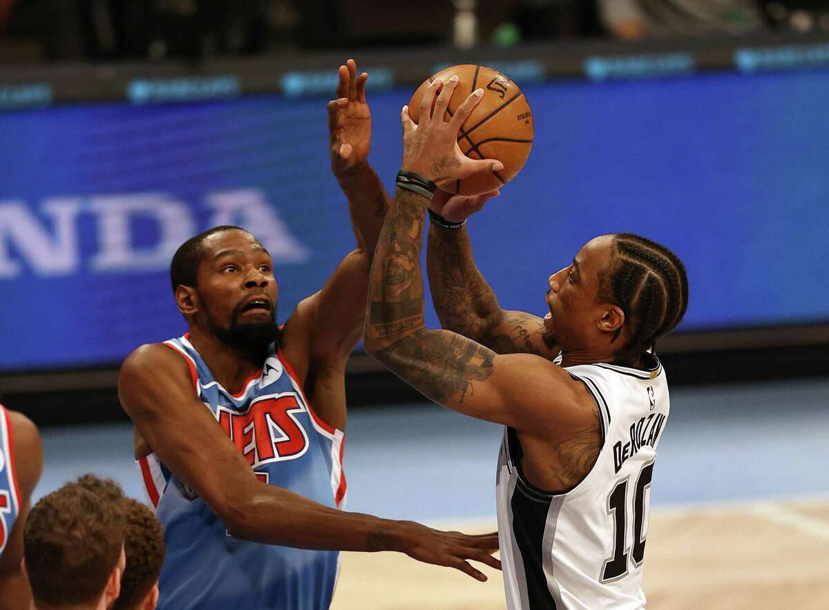 DeMar DeRozan (10) of the Spurs heads for the net as Kevin Durant of the Nets defends at Barclays Center on May 12, 2021, in New York.