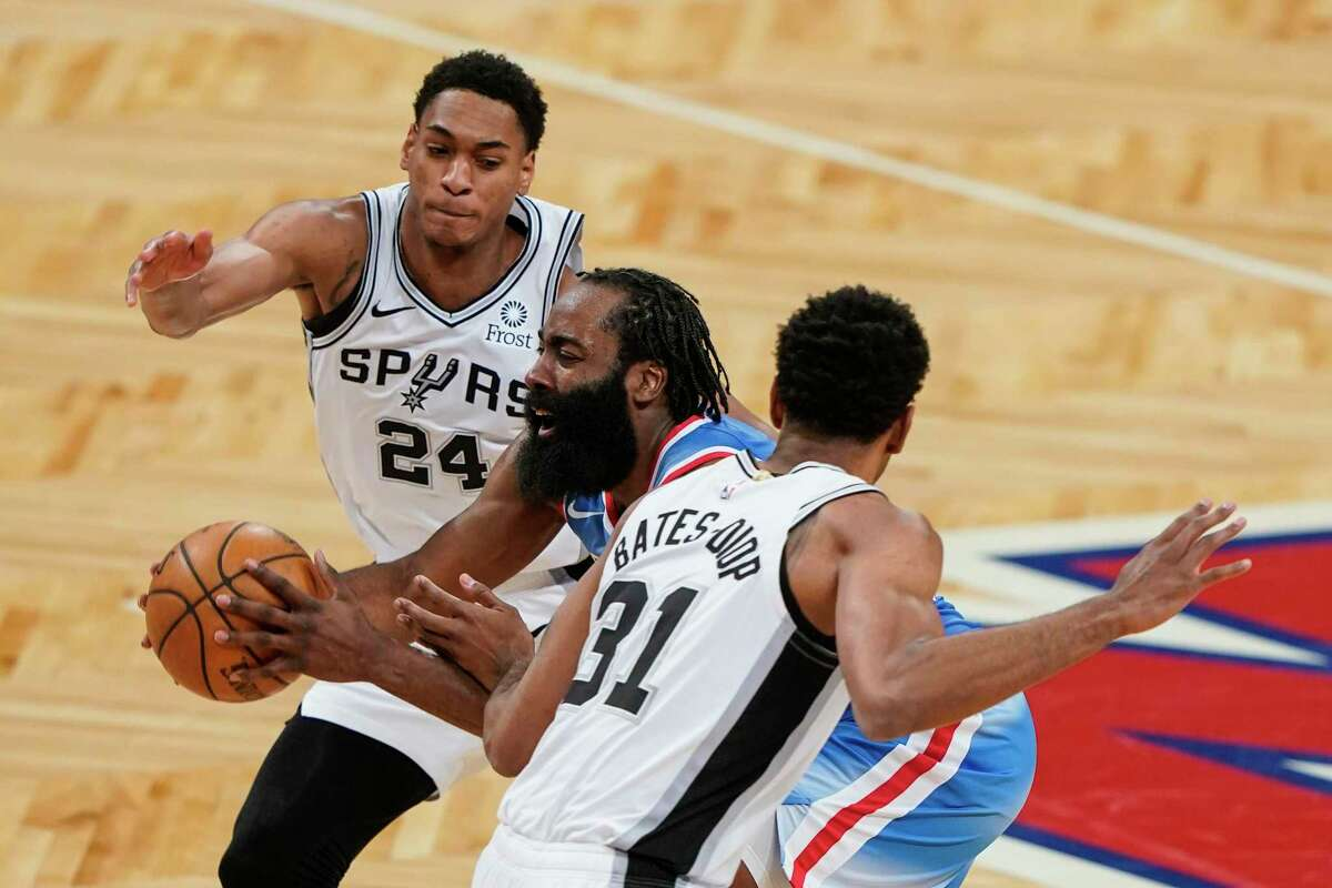 The Brooklyn Nets' James Harden, center, drives past the Antonio Spurs' Devin Vassell, left, and Keita Bates-Diop during the second half of an NBA basketball game Wednesday, May 12, 2021, in New York.