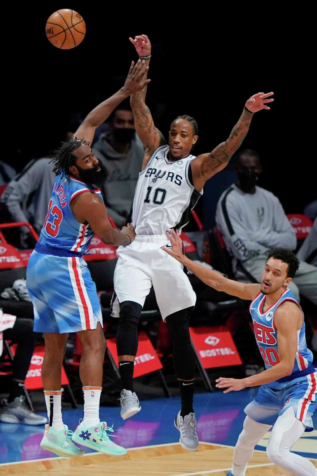 The Spurs' DeMar DeRozan (10) passes away from the Brooklyn Nets' James Harden (13) and Landry Shamet (20) during the second half of an NBA basketball game Wednesday, May 12, 2021, in New York.