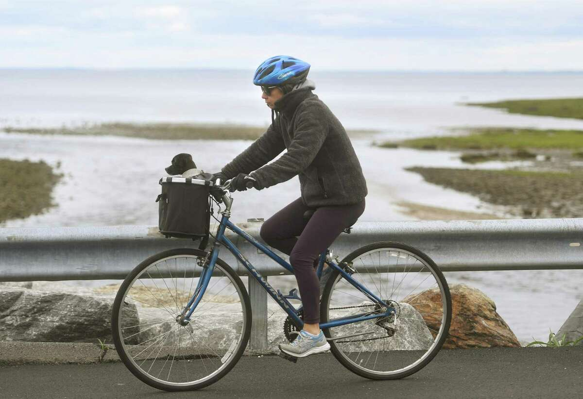 A woman rides her bike along Southport Beach on Pequot Avenue in Fairfield, Conn. on Monday, May 10, 2021.