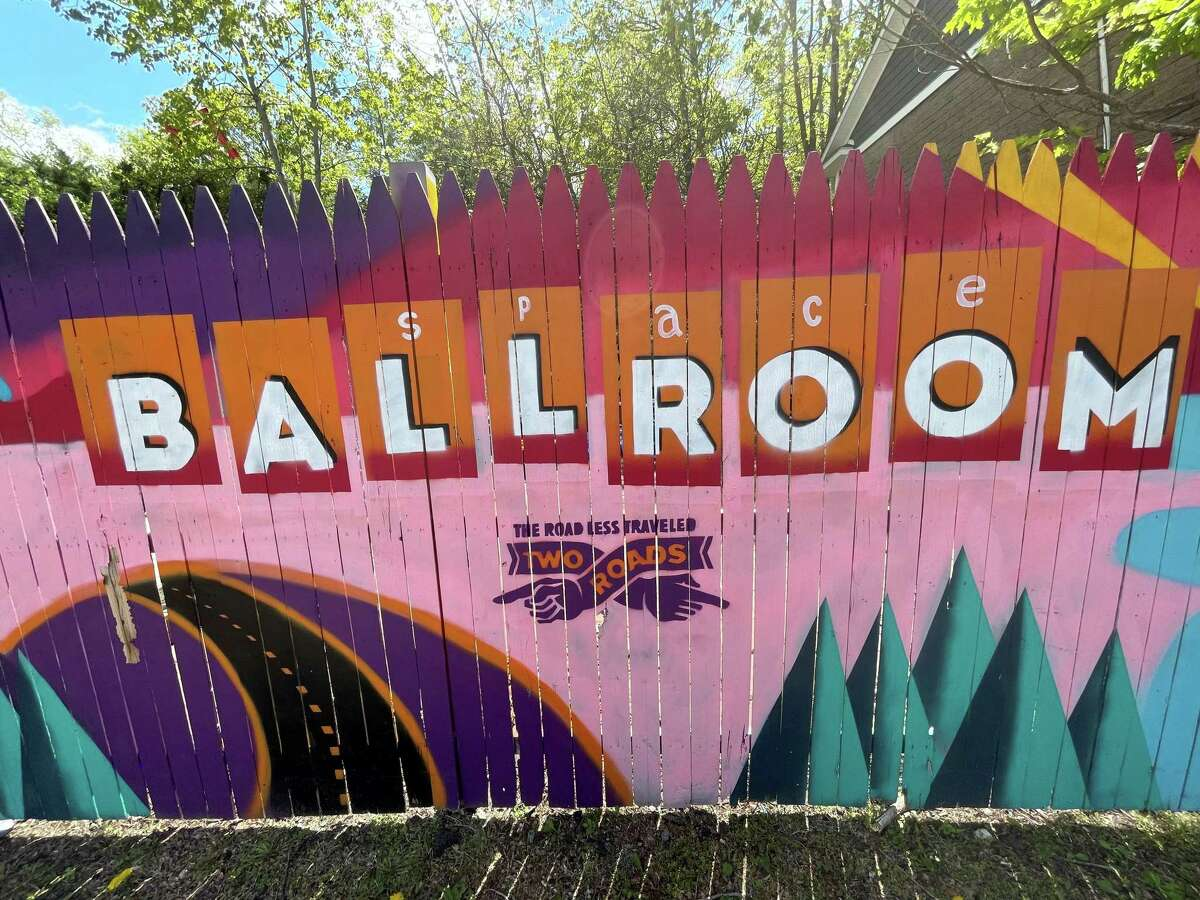 A painted fence next to Hamden's Space Ballroom.