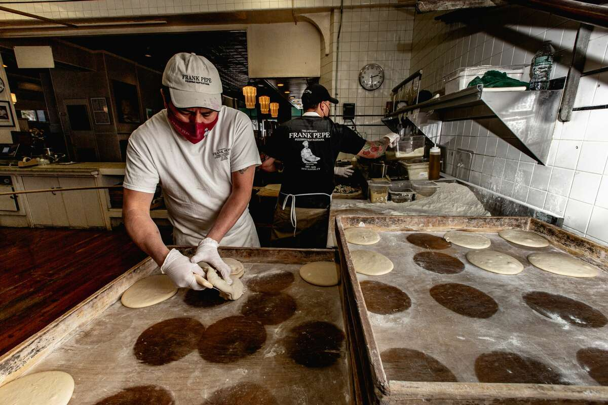 A pizza maker picks up fresh pizza dough at Frank Pepe's on April 23, 2021.