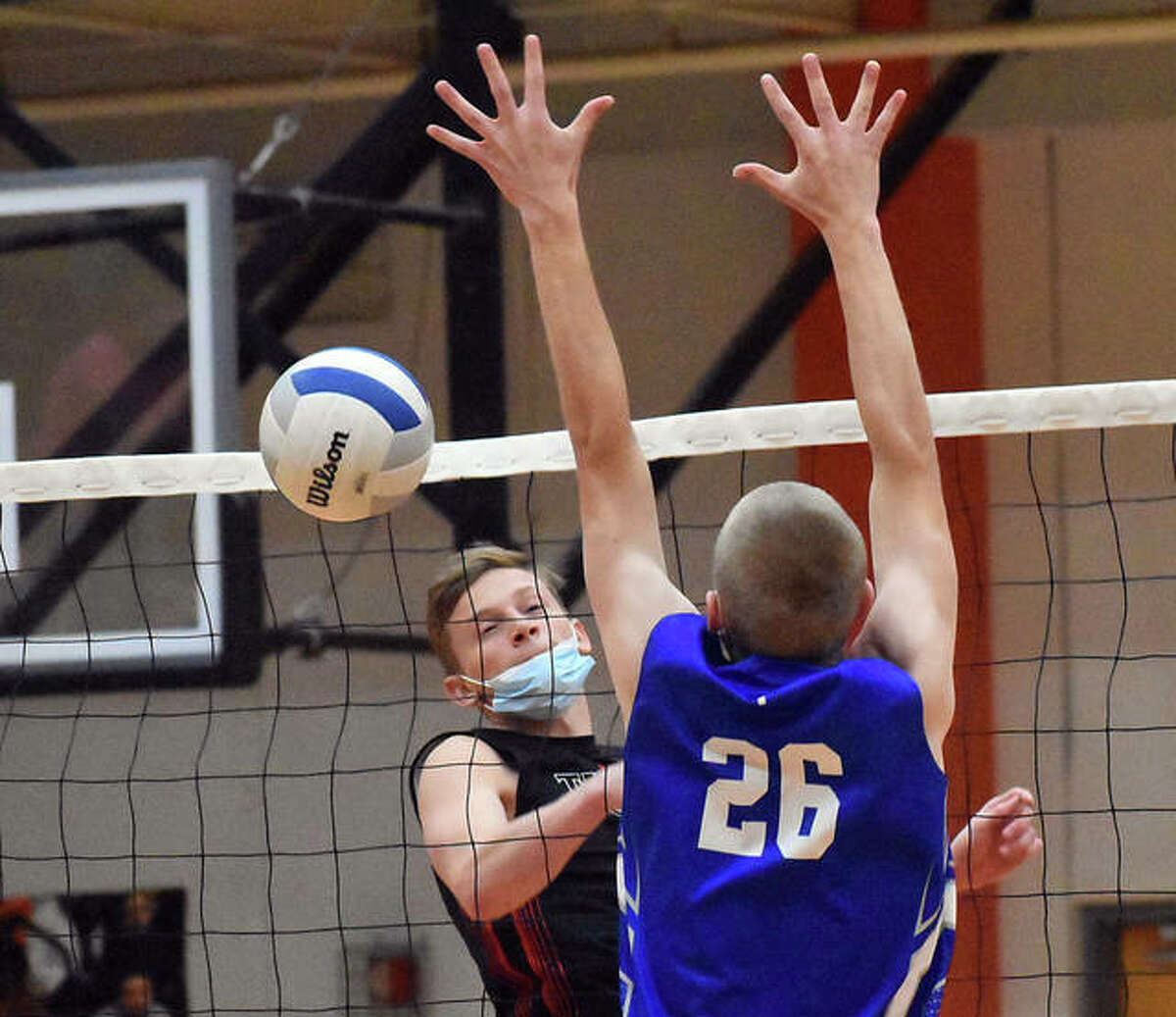 Edwardsville's Preston Weaver tips an attack over the net for a point in the first game against Marquette Catholic on Wednesday inside Lucco-Jackson Gymnasium in Edwardsville.