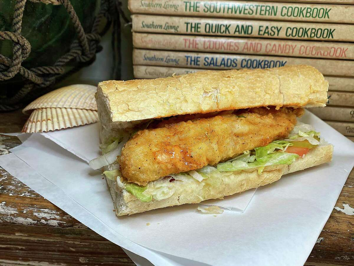 A catfish po'boy comes with lettuce, tomato, pickles, mayo and housemade spicy Carter sauce at Paris St. Po'Boys in Castroville.