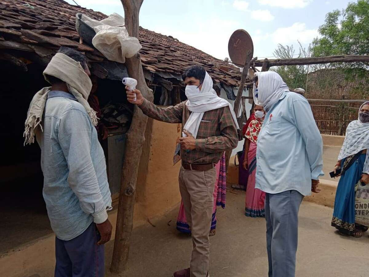 Community workers perform COVID-19 surveillance in India.