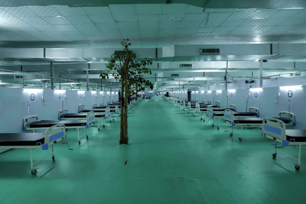 A tree stands at a facility for COVID-19 patients with 500 ICU beds that is being set up at Ramlila ground, a usual venue of major political rallies in New Delhi, India, Wednesday, May 12, 2021. (AP Photo/Amit Sharma)