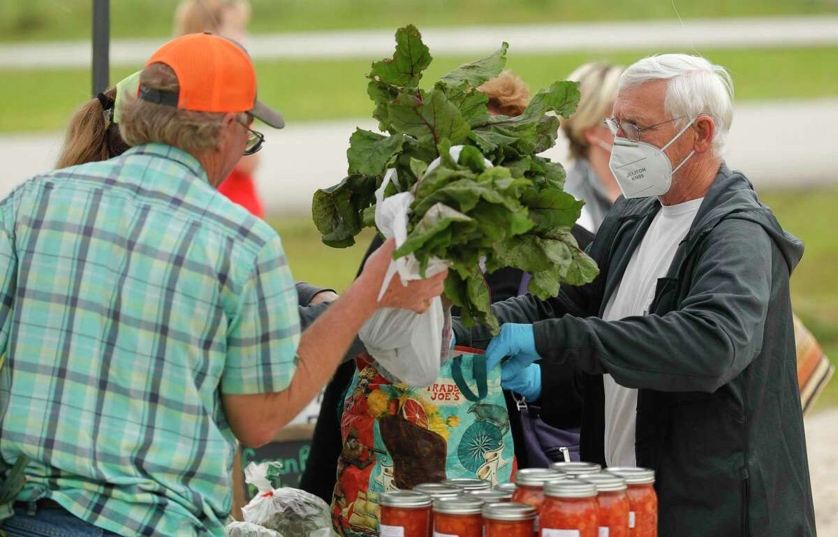 Mike Cooley shops for fresh produce with his wife, Tobi, at the Farmer's Market on Tamina, Saturday, April 18, 2020, in Magnolia.