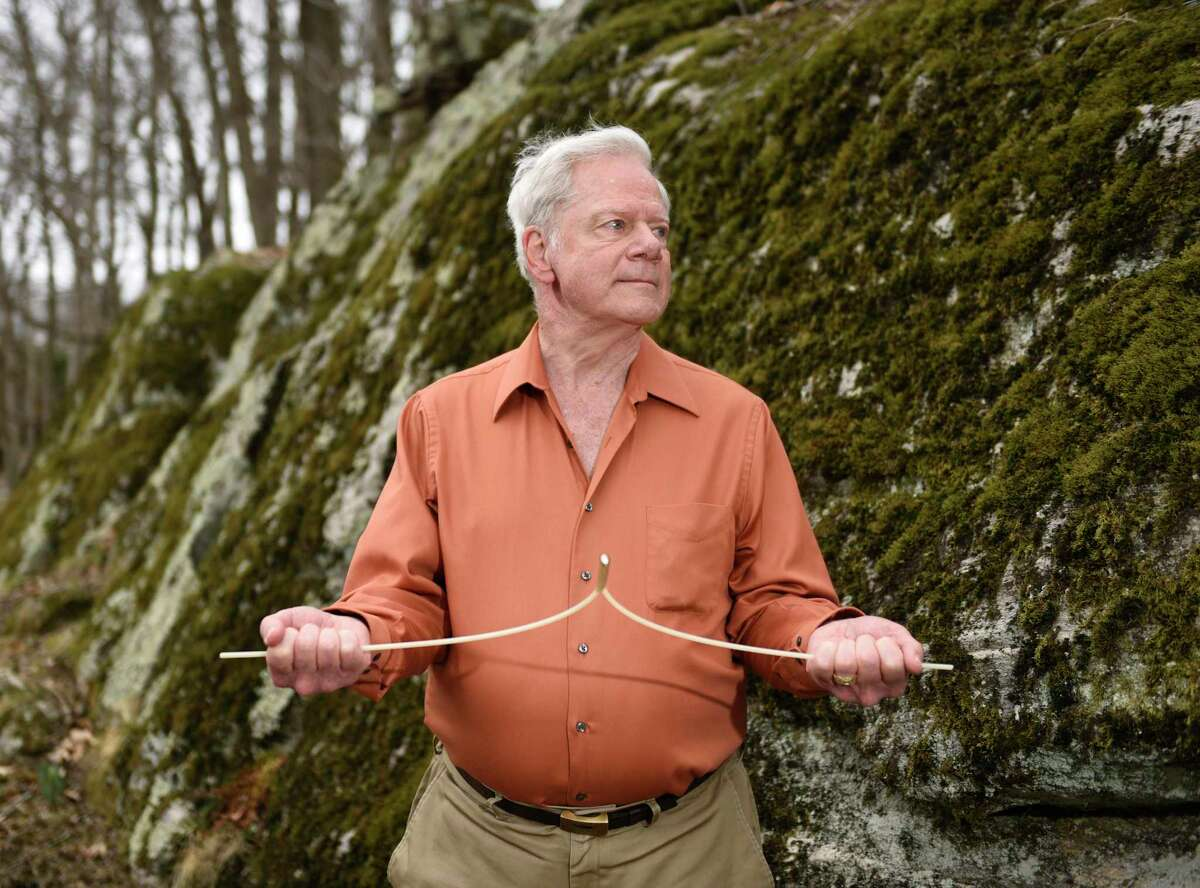 Master dowser Leroy Bull demonstrates his dowsing technique in the woods of Stamford, Conn. Wednesday, March 24, 2021. Dowsing is a spritual technique used to search for underground water, minerals, or lost items often using a forked stick or L-shaped dowsing rods. Bull is a Stamford resident and a past President of The American Society of Dowsers.