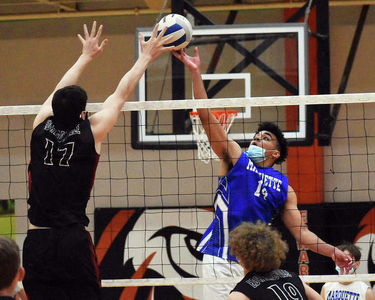 Marquette Catholic's Davin Thompson (right) tips a shot over the block of Edwardsville's John Kreke during the second game on Wednesday inside Lucco-Jackson Gymnasium in Edwardsville.