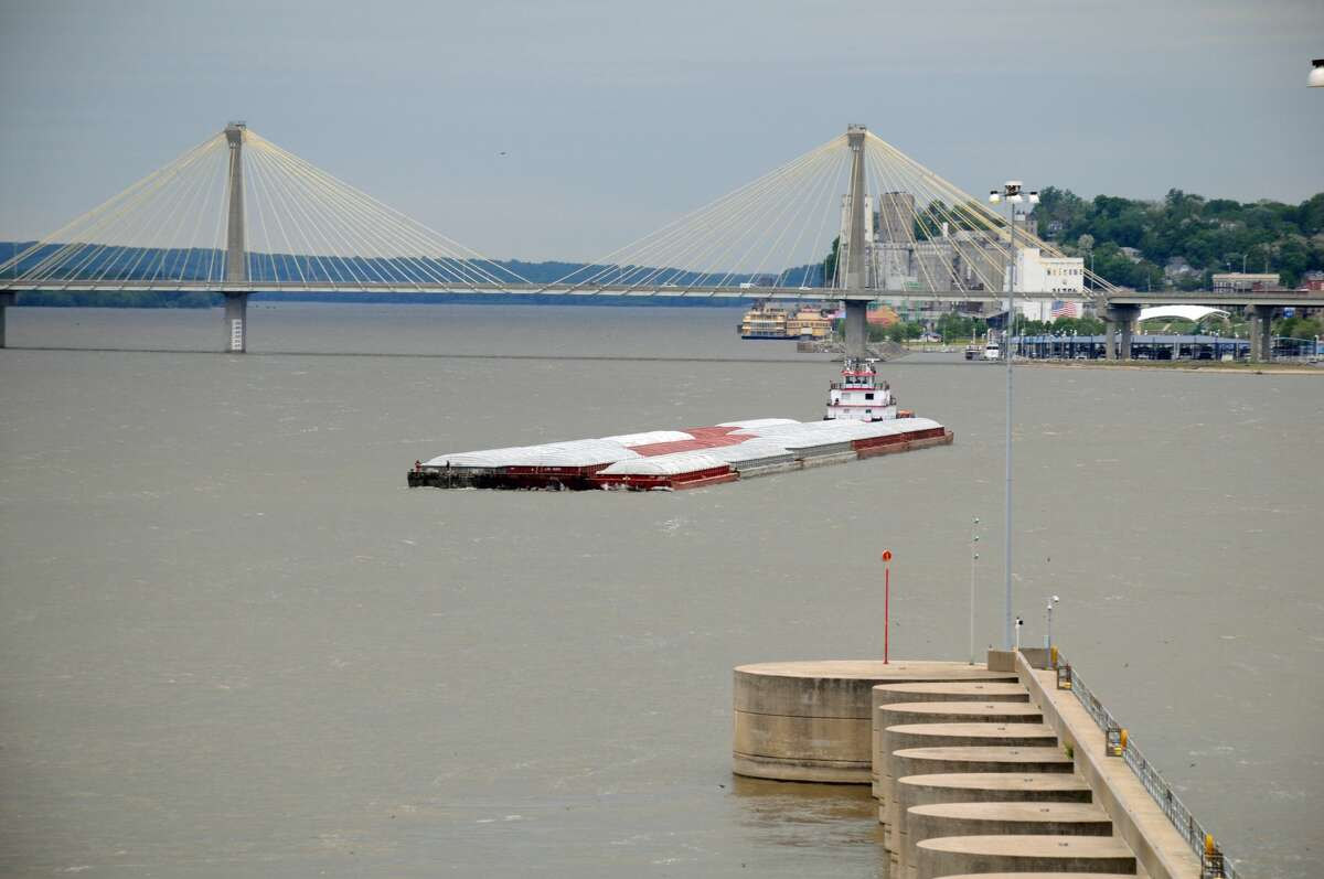 A towboat with a load of barges approaches the upriver lock with the Clark Bridge in the background.