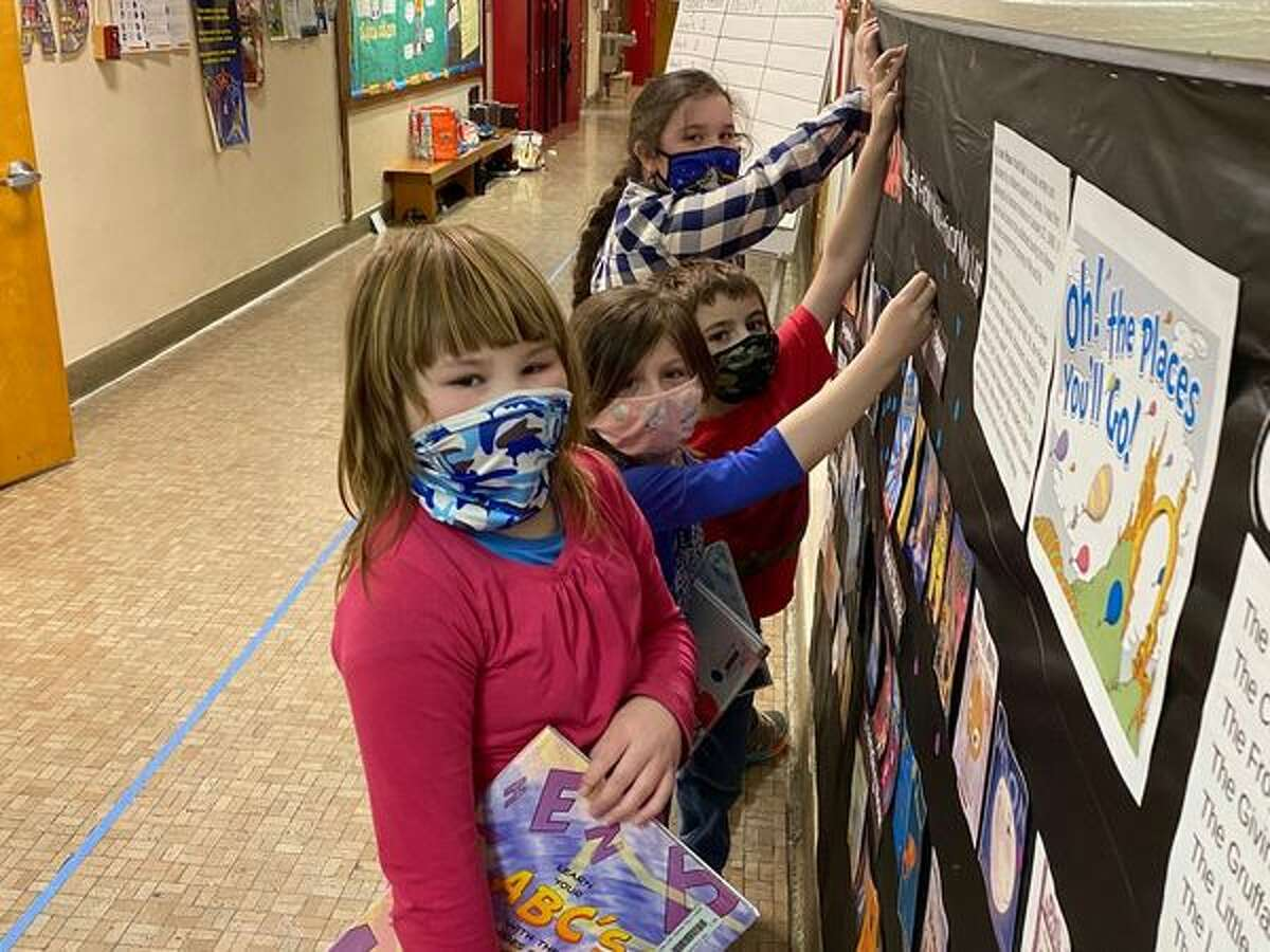 First graders at Long Lake Central School District in the Adirondacks add stickers to a bulletin board. Educators want more guidance on if schools will be required to be in-person in fall 2021, or if there will still be a remote option provided to students.