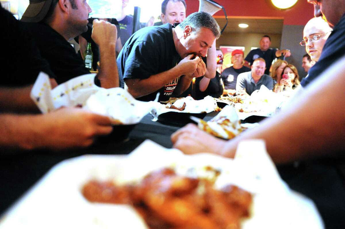Stamford Police's Joe Rainone in action as city police officers and firefighters square off in the Guns-n-Hoses Blazin Wing Eating Contest at Buffalo Wild Wings on Summer Street Thursday, September 30, 2010.
