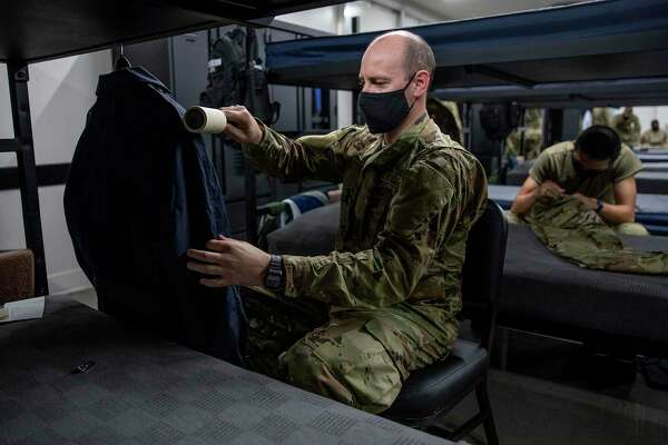 Airman Basic Michael Branham carefully removes lint from his uniform during a break in his dorm at Joint Base San Antonio-Lackland. The number of trainees in each dorm was reduced when the pandemic arrived, to allow social distancing.