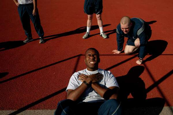 Airman Basic Robert Harris finishes his situp requirements for the final PT test at Joint Base San Antonio-Lackland while his wingman Ian Peskar keeps count.